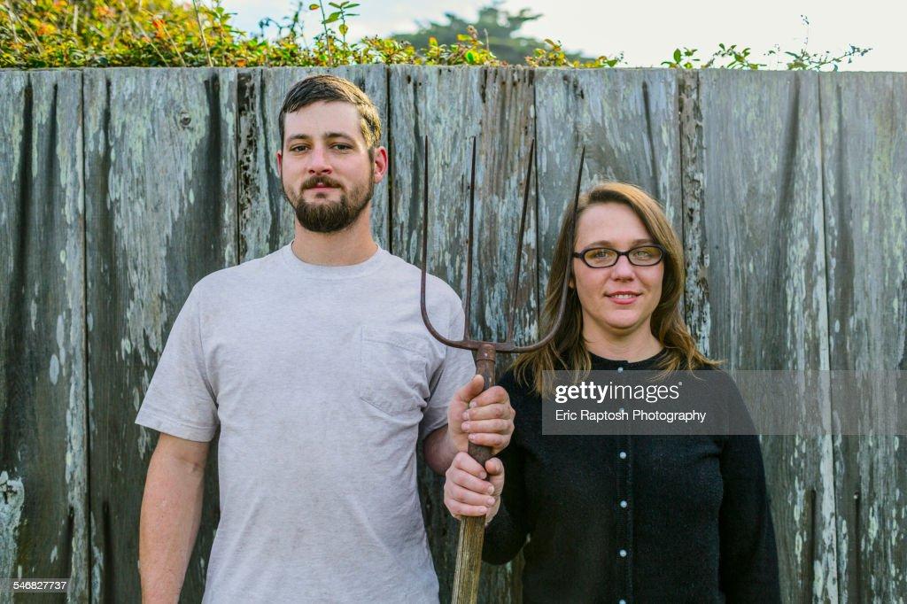 Caucasian couple holding pitchfork near fence