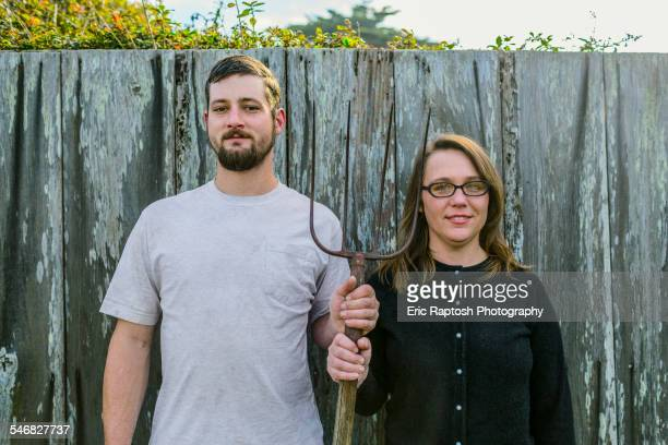 Caucasian couple holding pitchfork near fence