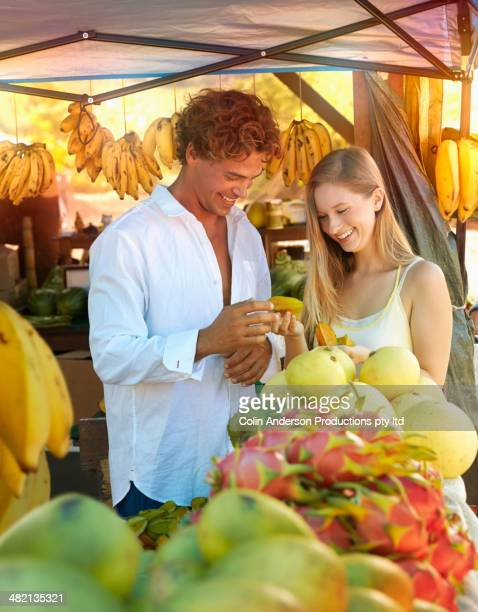 Caucasian couple holding star fruit at produce stand