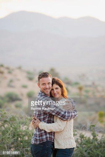 Caucasian couple hugging in desert