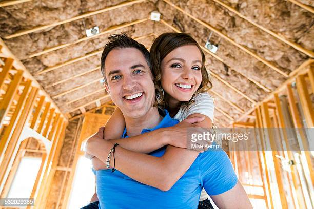Caucasian couple hugging in house under construction