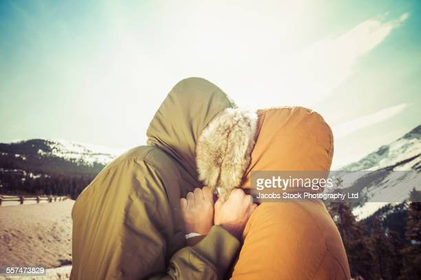 Caucasian couple hugging in parka hoods near mountain