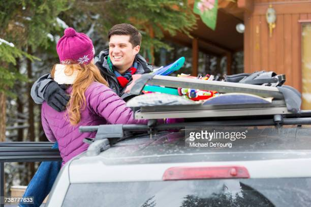 Caucasian couple hugging near snowboards in car roof rack