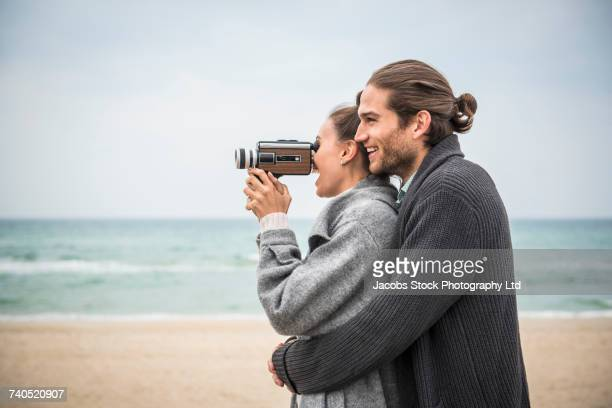 Caucasian couple hugging on beach and using video camera
