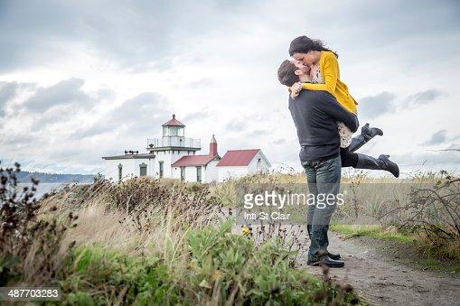 Caucasian couple hugging on beach path