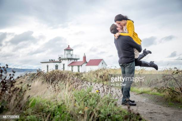 Caucasian couple hugging on beach path