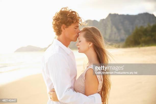 Caucasian couple hugging on beach