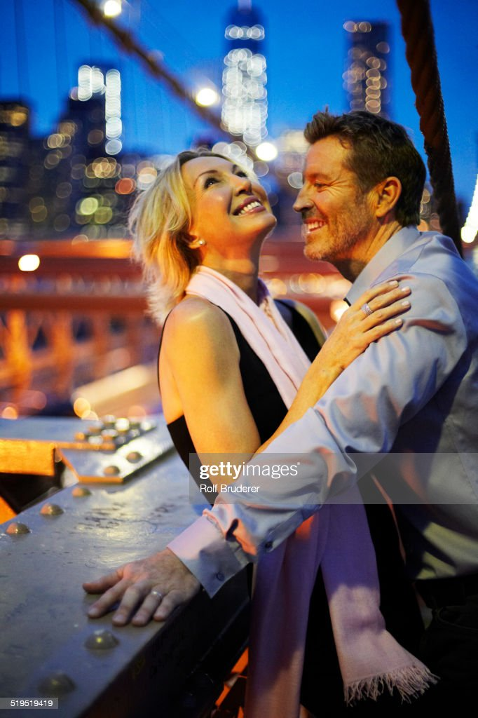 Caucasian couple hugging on Brooklyn Bridge, New York City, New York, United States