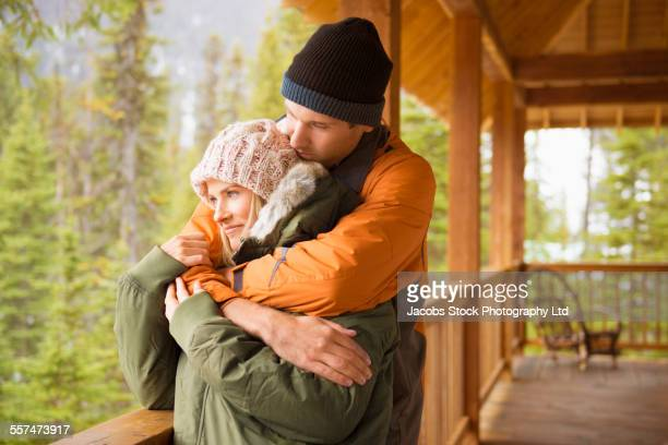 Caucasian couple hugging on log cabin porch