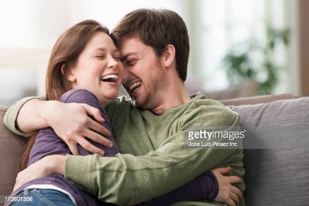 Caucasian couple hugging on sofa