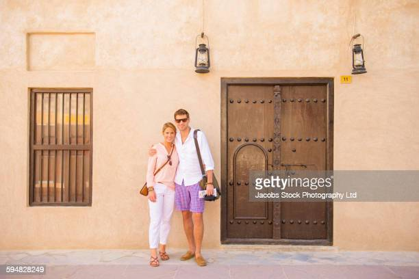 Caucasian couple hugging outside building