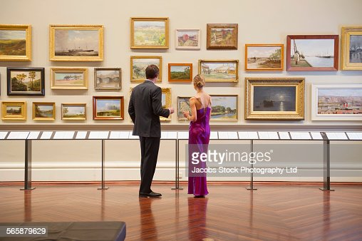Caucasian couple in evening wear admiring art in museum