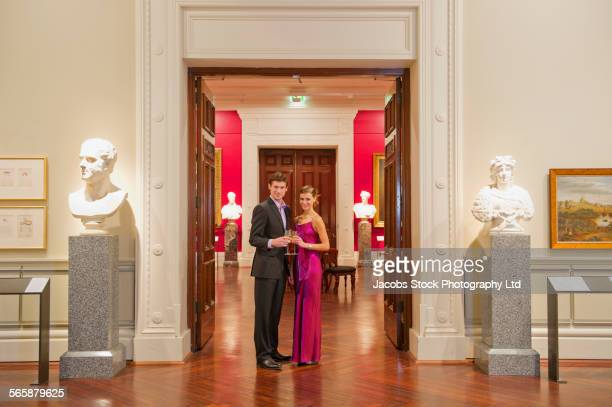 Caucasian couple in evening wear smiling in art museum