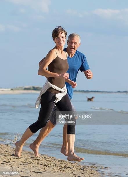 Caucasian couple jogging on beach