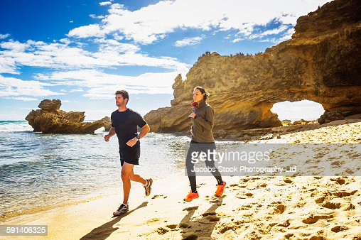 Caucasian couple jogging on beach