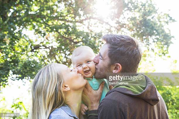 Caucasian couple kissing baby in backyard