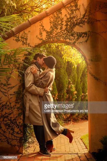 Caucasian couple kissing in archway