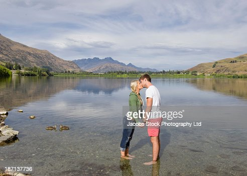 Caucasian couple kissing in rural lake : Stock Photo
