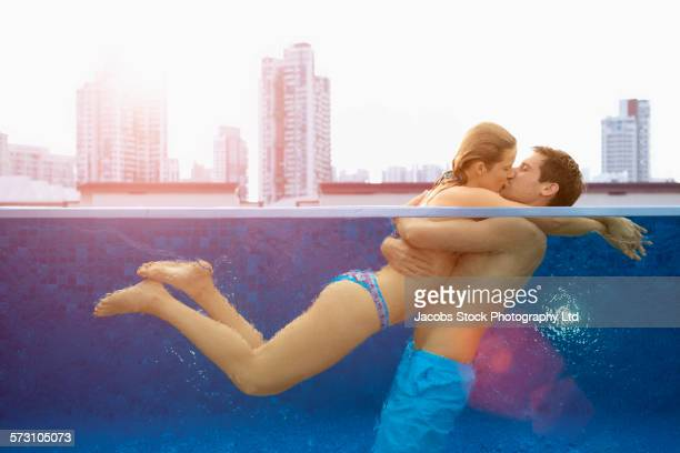 Caucasian couple kissing in urban rooftop swimming pool, Singapore