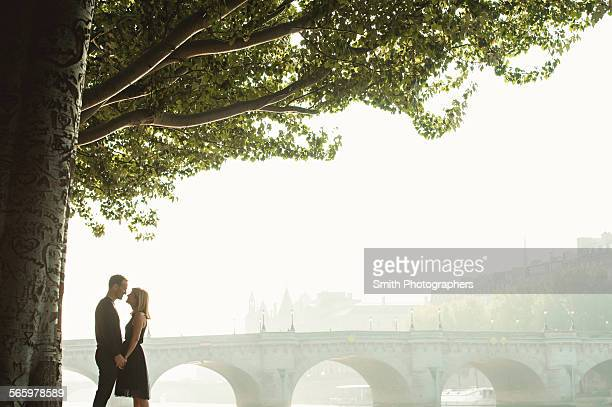 Caucasian couple kissing near bridge, Paris, Ile-de-France, France