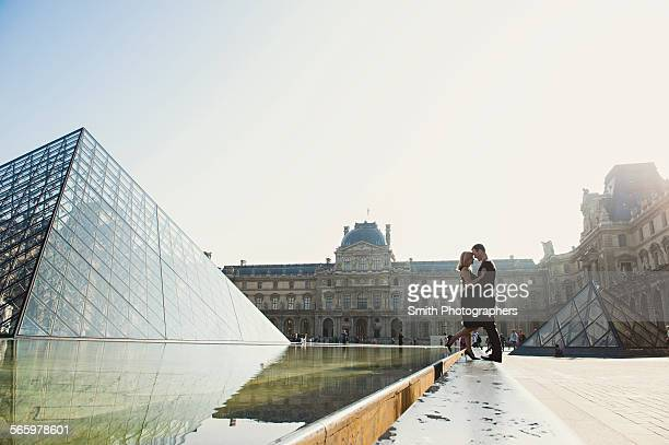 Caucasian couple kissing near ornate building, Paris, Ile-de-France, France