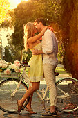 Caucasian couple kissing on bicycle