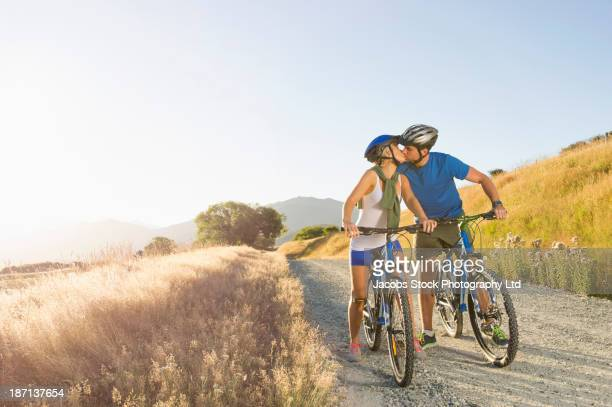 Caucasian couple kissing on rural road
