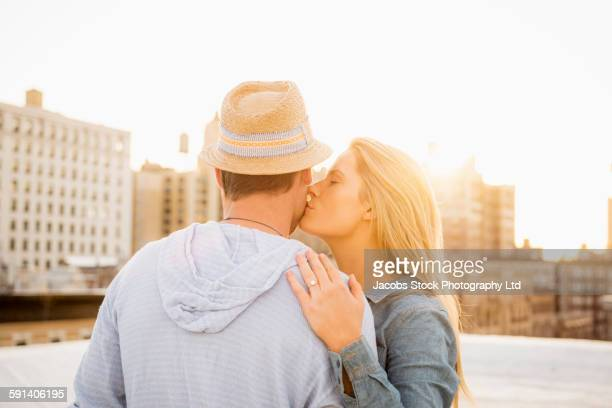 Caucasian couple kissing on urban rooftop