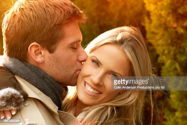 Caucasian couple kissing outdoors