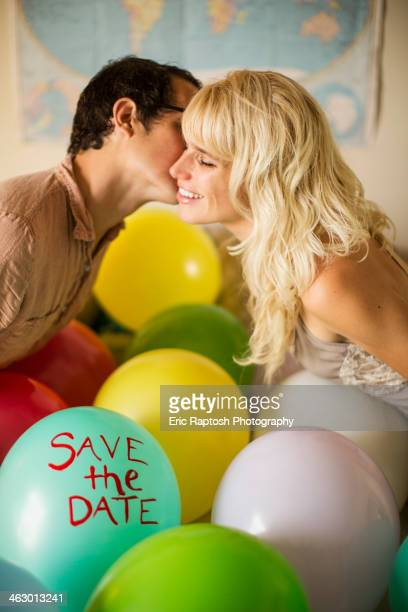 Caucasian couple kissing over balloon with 'save the date'' text