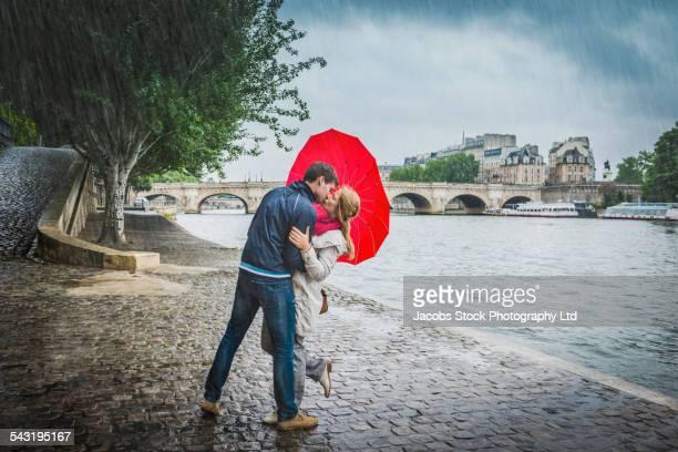 Caucasian couple kissing under heart shape umbrella