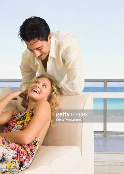 Caucasian couple laughing in living room