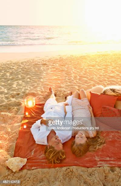 Caucasian couple laying on beach blanket