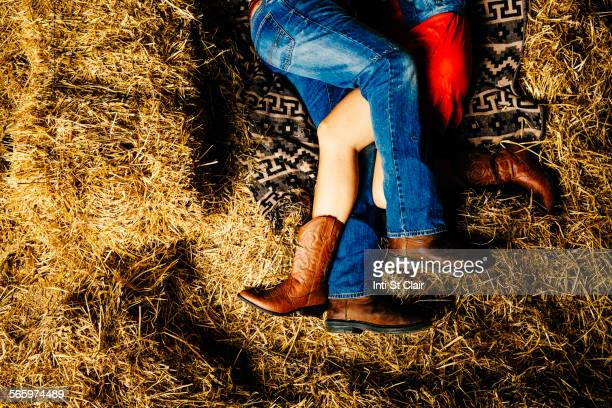 Caucasian couple laying on haystacks