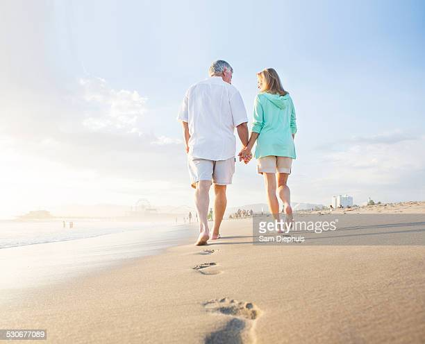 Caucasian couple leaving footprints on beach
