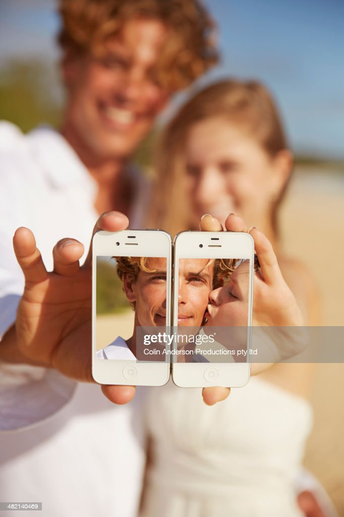 Caucasian couple making collage with cell phones : Stock Photo