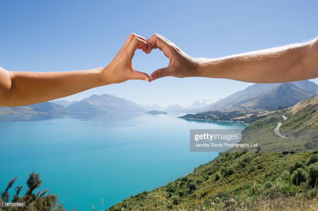 Caucasian couple making heart with hands in rural landscape : Stock Photo