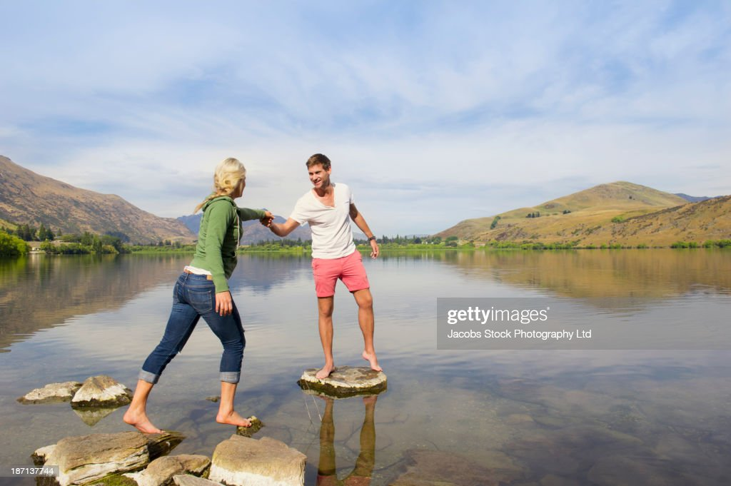 Caucasian couple on stones in rural lake : Stock Photo