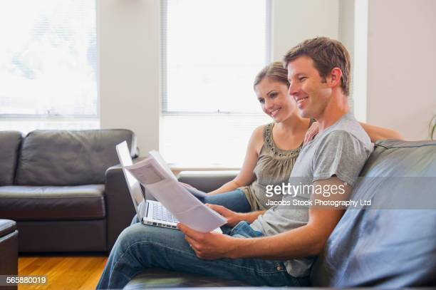Caucasian couple paying bills on laptop in living room