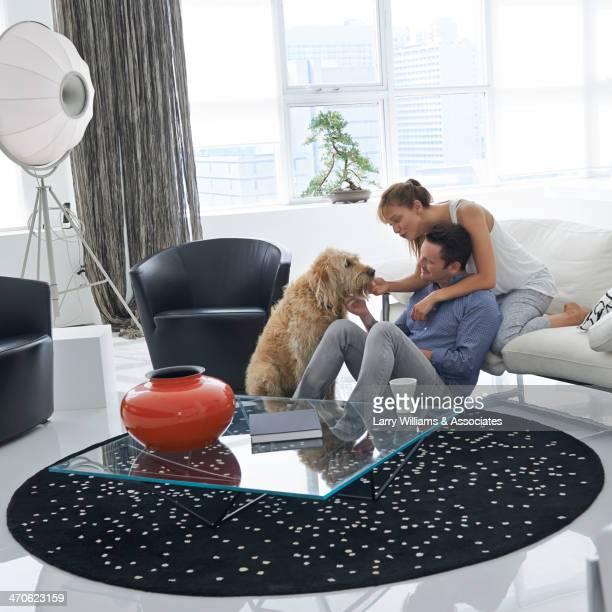 Caucasian couple petting dog in living room