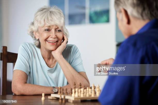 Caucasian couple playing chess together