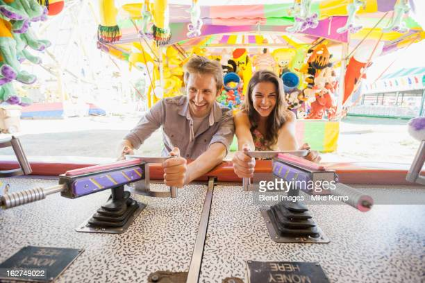 Caucasian couple playing games at carnival