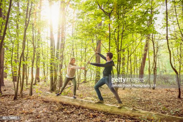 Caucasian couple playing in forest