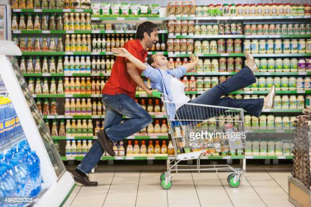 Caucasian couple playing in grocery store