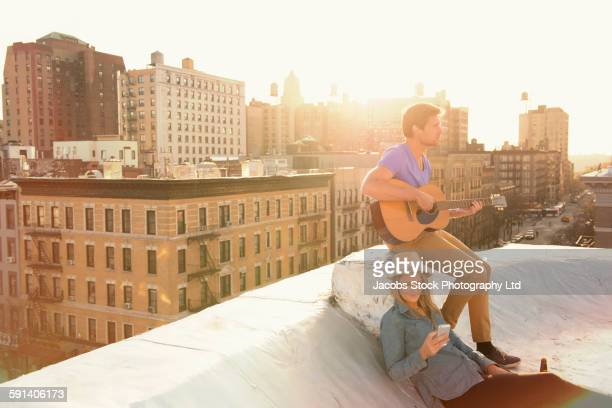 Caucasian couple playing music on urban rooftop
