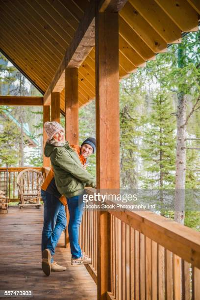 Caucasian couple playing on log cabin porch