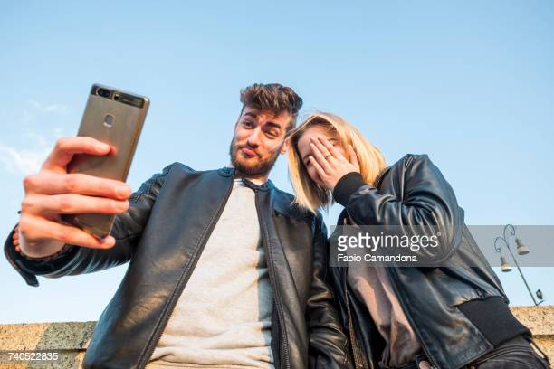 Caucasian couple posing for cell phone selfie