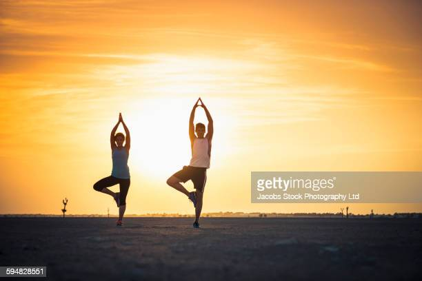 Caucasian couple practicing yoga in desert
