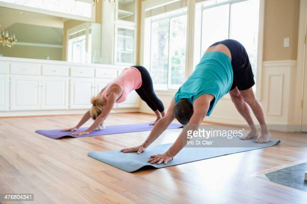 Caucasian couple practicing yoga in home