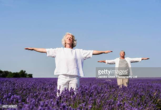 Caucasian couple practicing yoga in lavender field